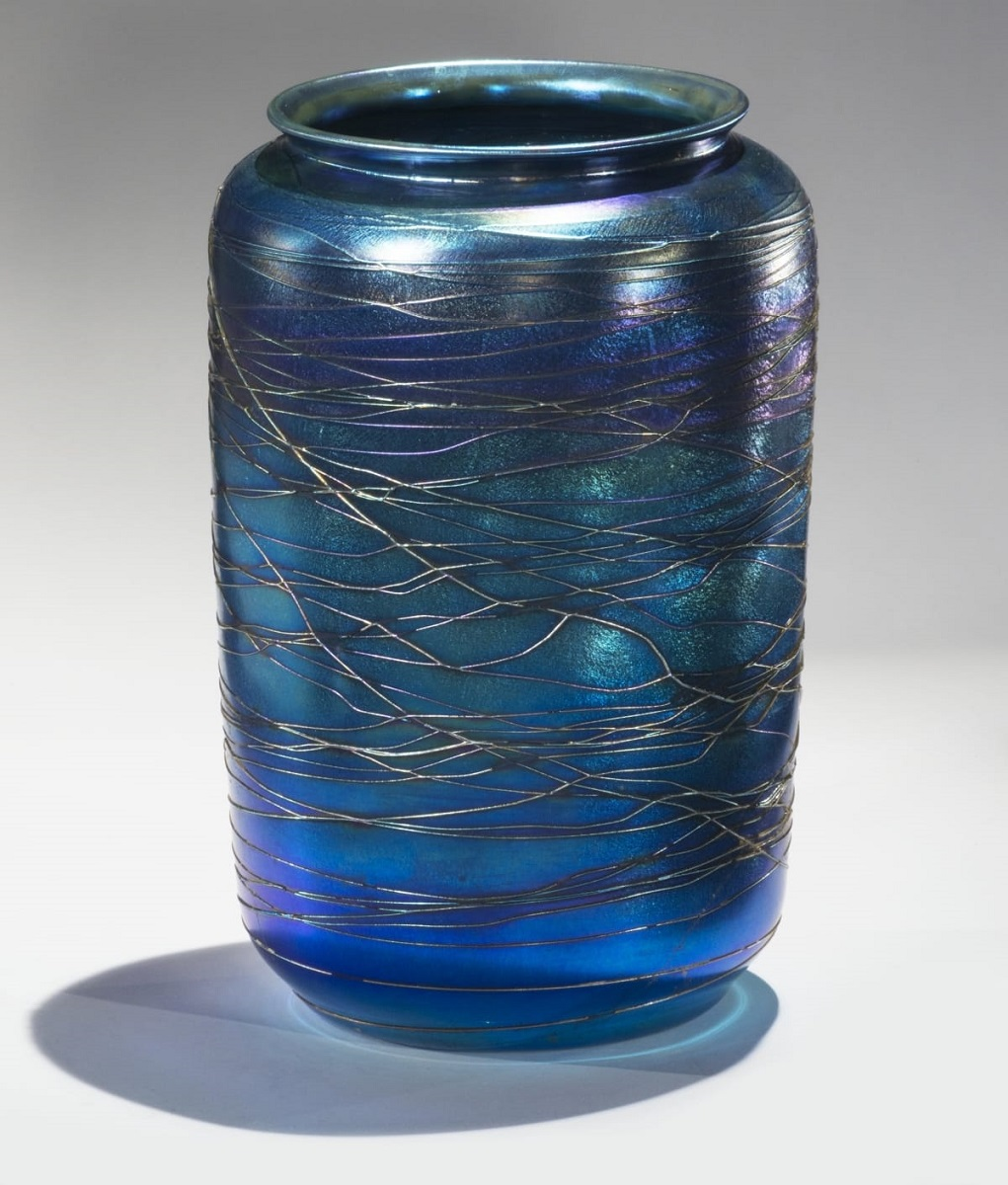 Wide blue glass vase with straight sides and wide opening, with pattern of lines running around it