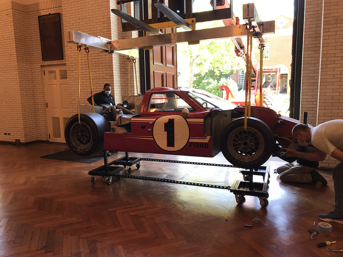 "Red race car with part of body removed and large ""1"" on side, suspended from a crane-like gantry in front of a large door; one person stands nearby and another examines the car"
