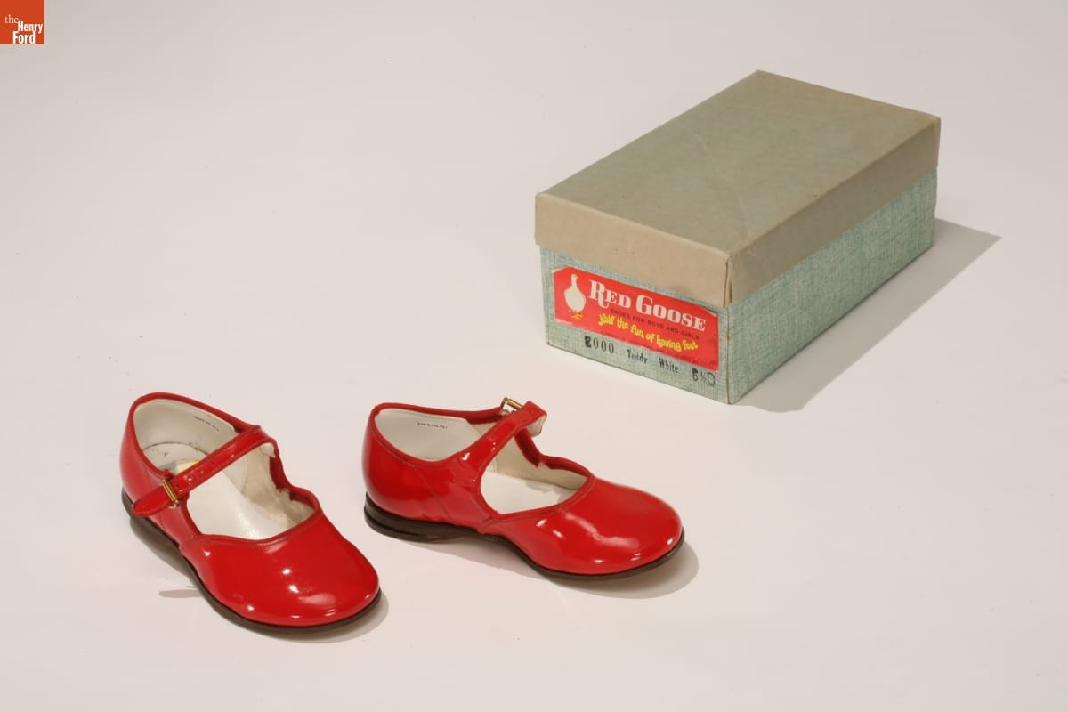 Shiny red shoes with a strap that would fall just in front of the ankle; blue shoebox next to them