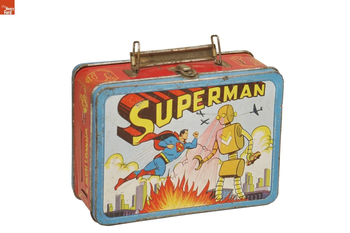 "Slightly rusted lunchbox with handle and front panel illustration of man in blue and red super hero outfit floating in air and fighting a large yellow robot shooting flames from its eyes; 3D text reading ""Superman"""
