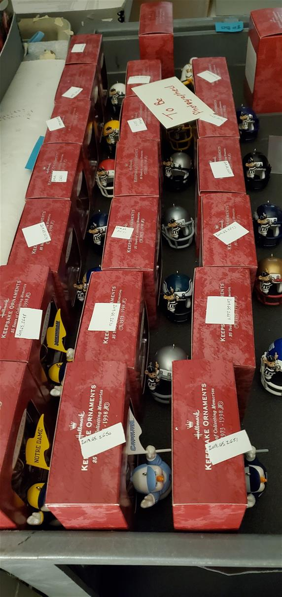 Red boxes lined up, with an ornament (mostly mini football helmets) in front of each