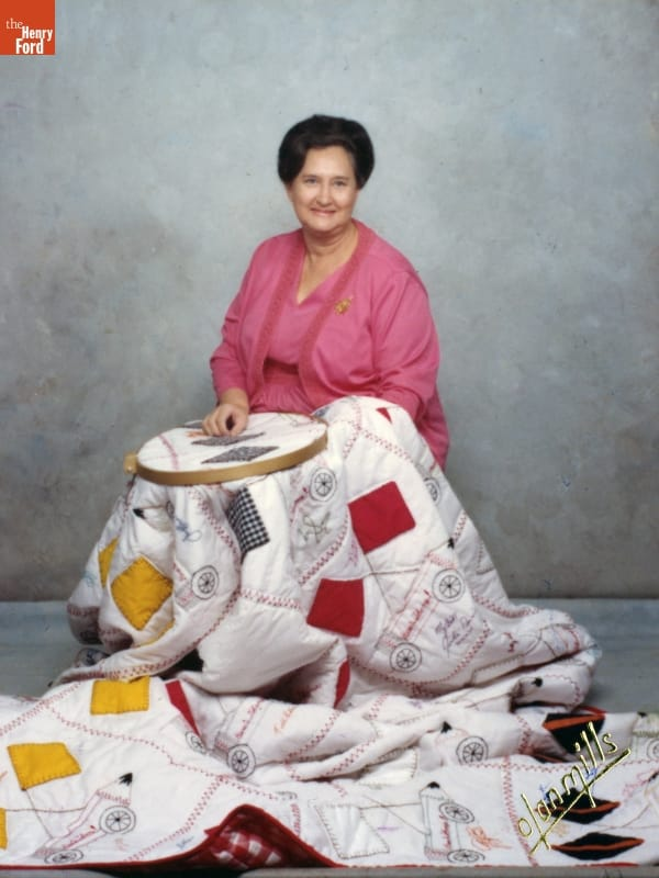 Woman with pink outfit and dark hair sits with a quilt over her, part of which is in a needlework frame on her lap