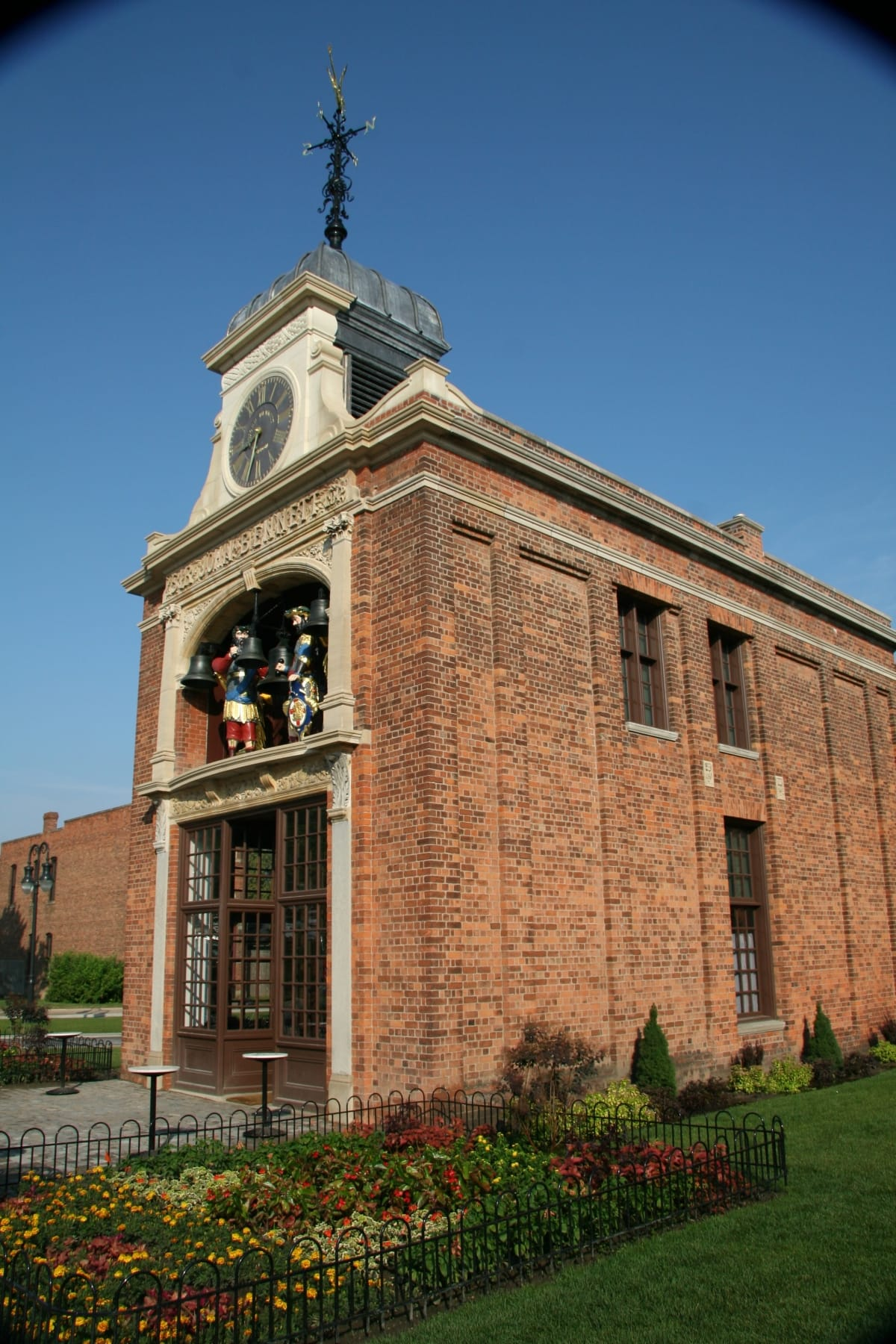 Narrow, two-story brick building with facade featuring oversize figures and a clock