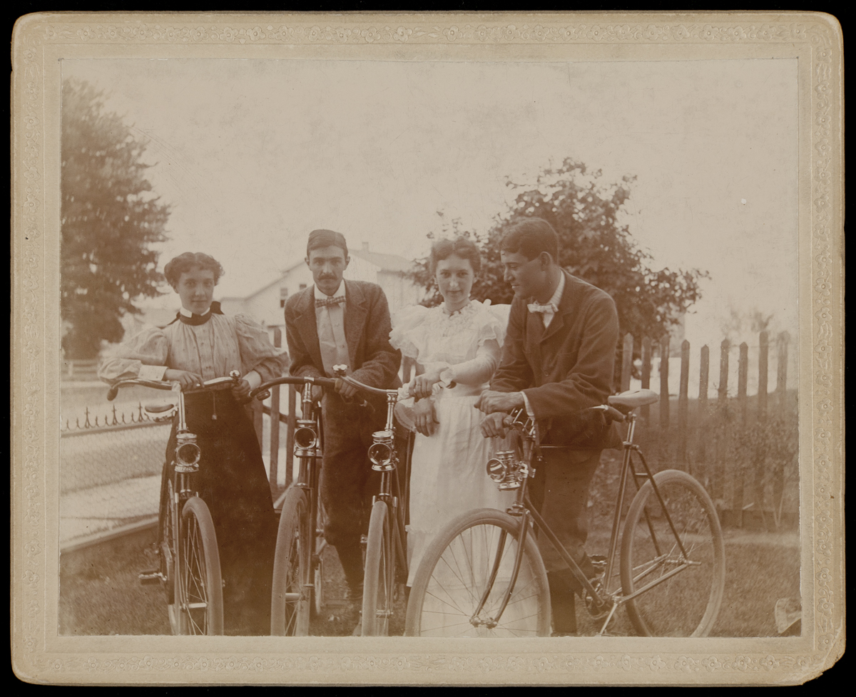 Two women in dresses and two men in suits, each standing next to a bicycle