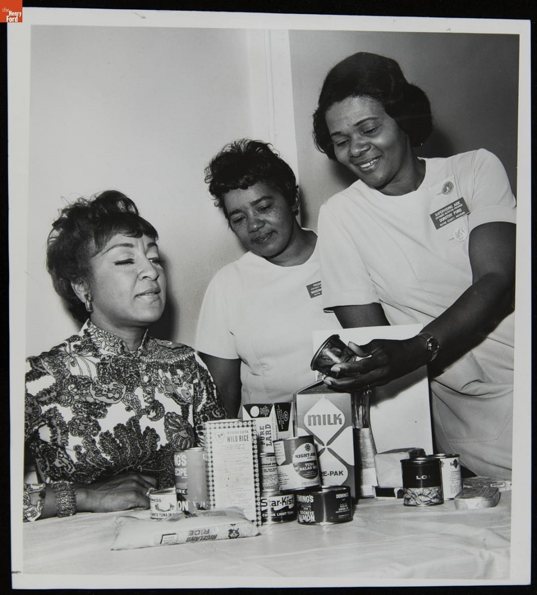 Three Black women sit and stand around a table that holds food packages