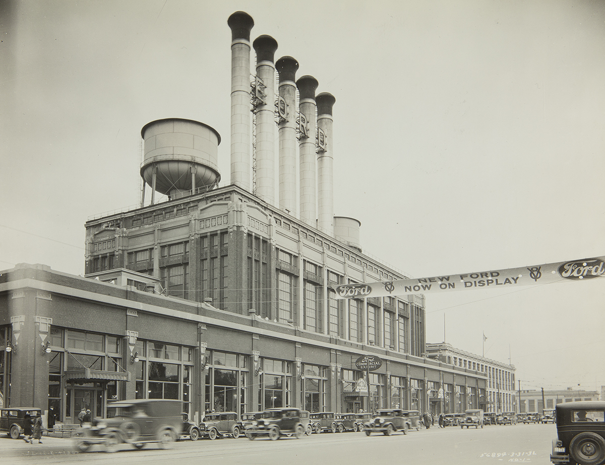 Factory topped with several smokestacks and a water tower, with cars driving by in front