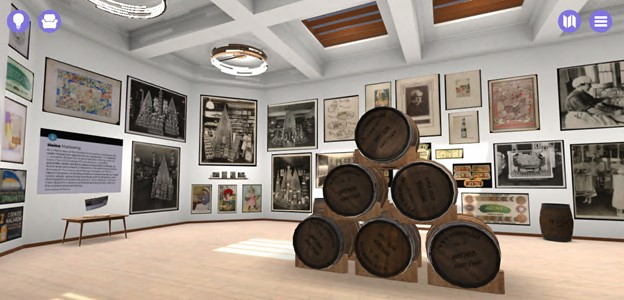 Virtual room with wooden floor and white walls covered with images; stacked barrels in the center of the room