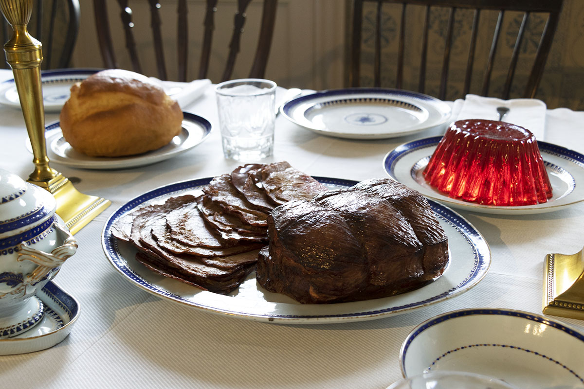 Meat roast (partially sliced), jello mold, and round loaf of bread on plates on table, with place settings nearby