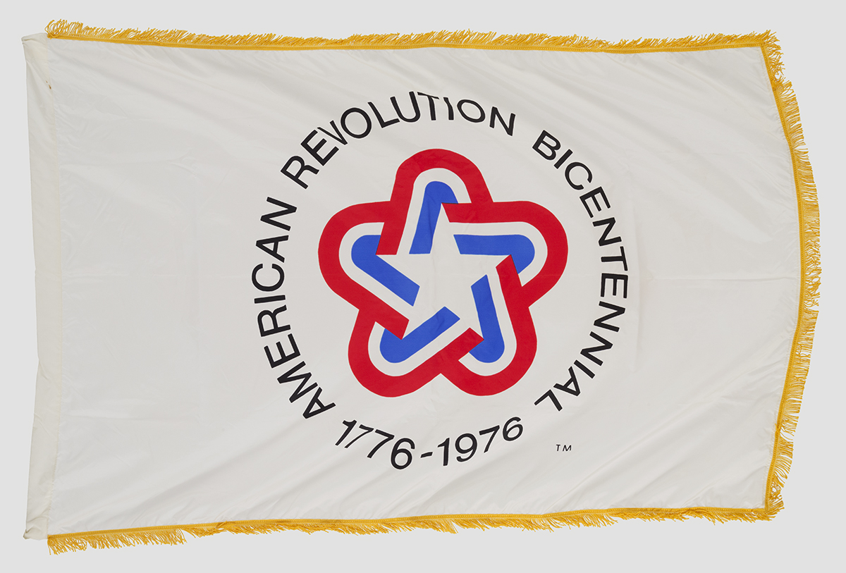 "Gold-fringed white flag with rounded star in red, white, and blue and text ""American Revolution Bicentennial 1776-1976"""