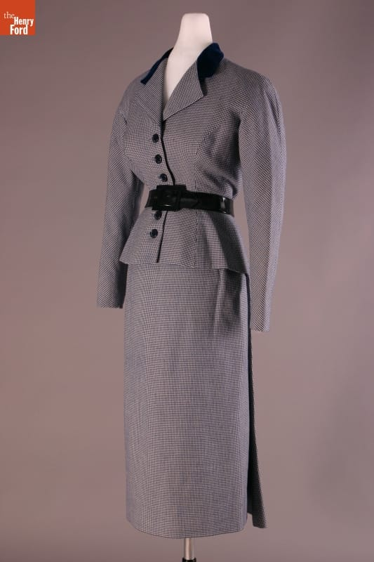 Long gray skirt and gray jacket with black belt, buttons, and collar