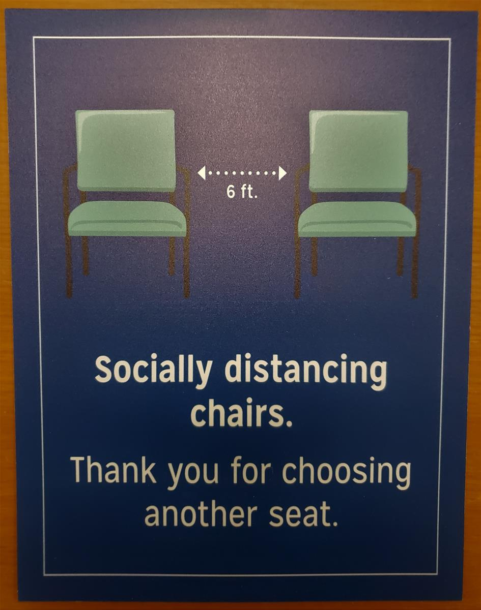 Poster showing two green chairs with dotted lines denoting six feet between them; also contains text