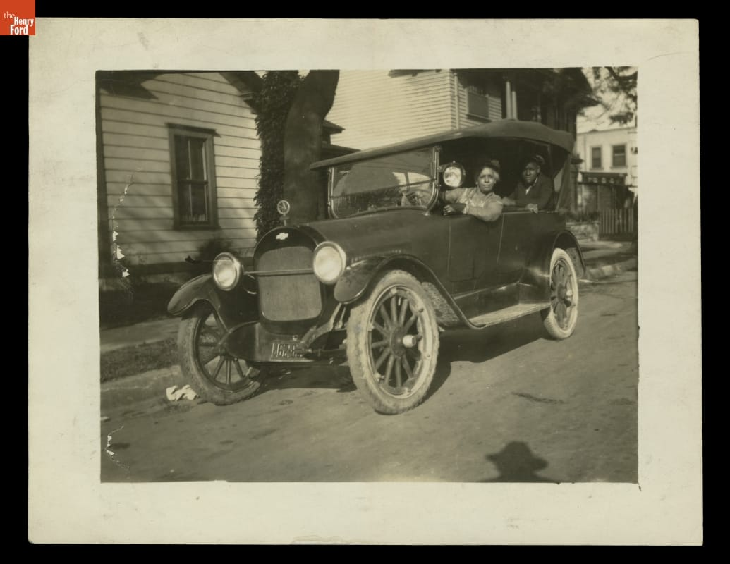 Woman at wheel of old-fashioned car with man visible in seat behind her; houses behind them