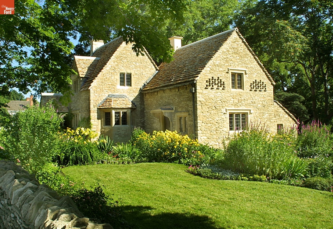 Stone house with green lawn and lush flower garden