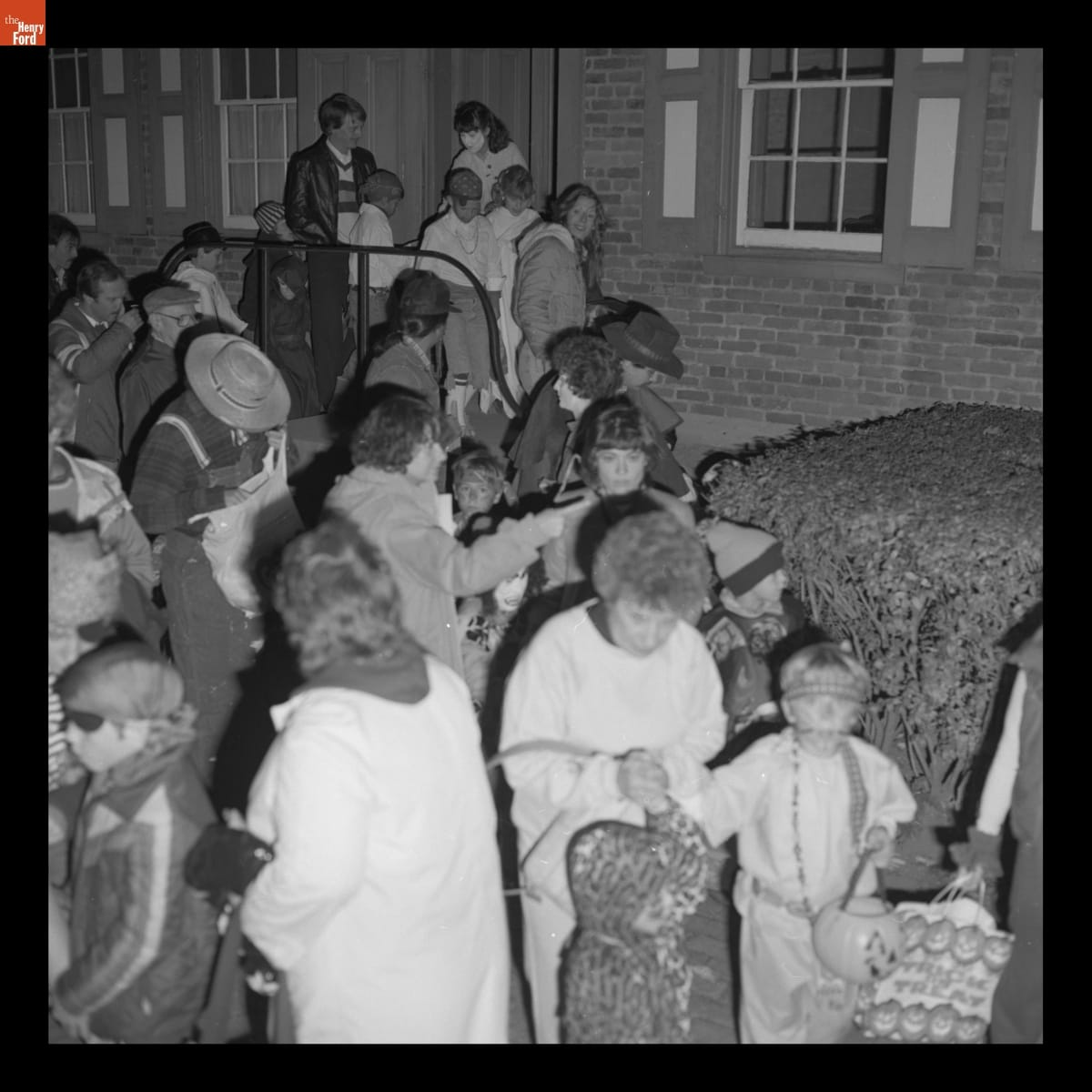 Crowd of adults and children, many in costume, outside brick house