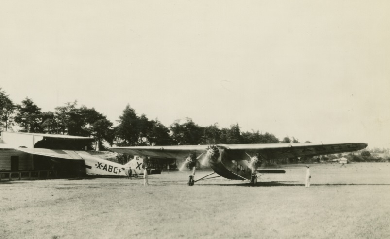 Two planes and several people in open field near low building