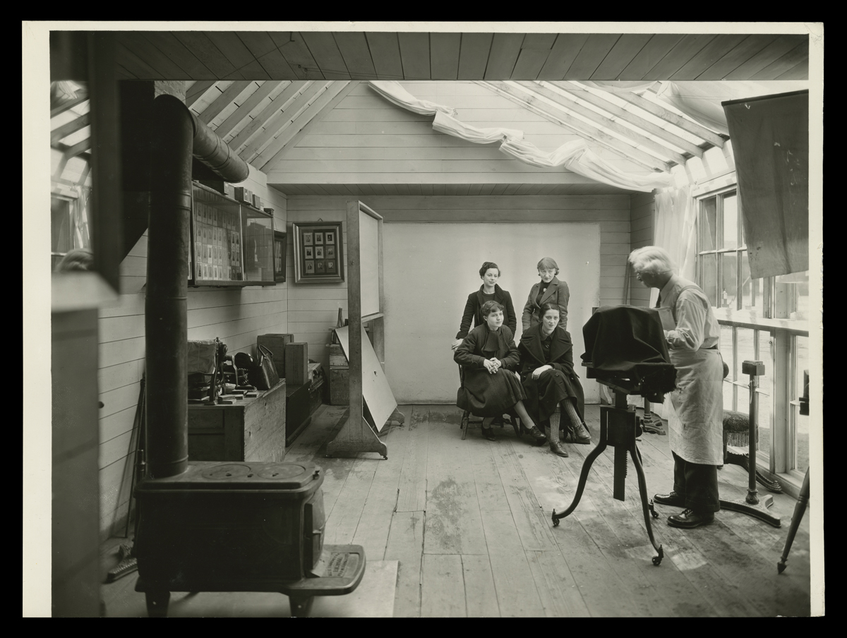 Room with photographer at camera pointed at four women posing; woodstove in foreground and images on walls