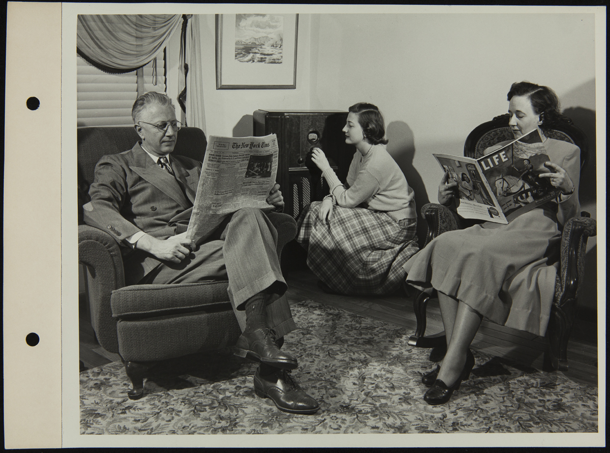 Man and woman sitting in chairs, reading, while teen girl kneels by a radio