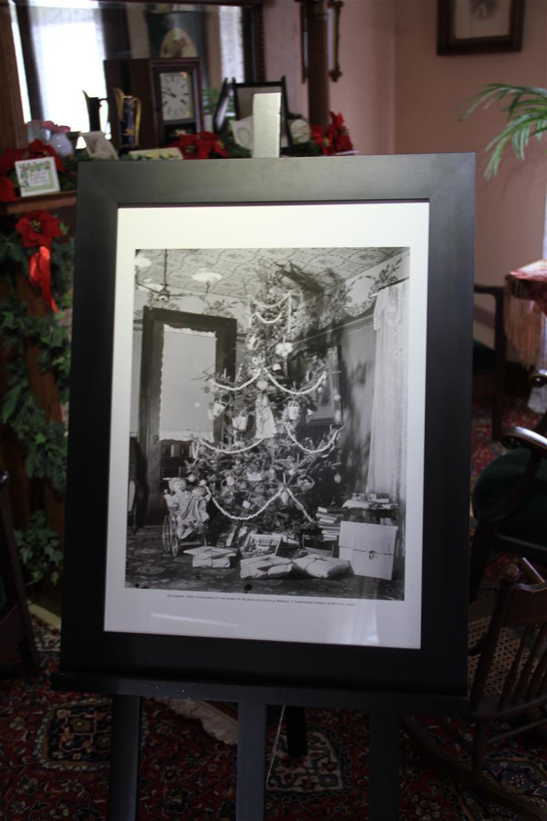 Large framed black-and-white photograph showing a Christmas tree on an easel in a room
