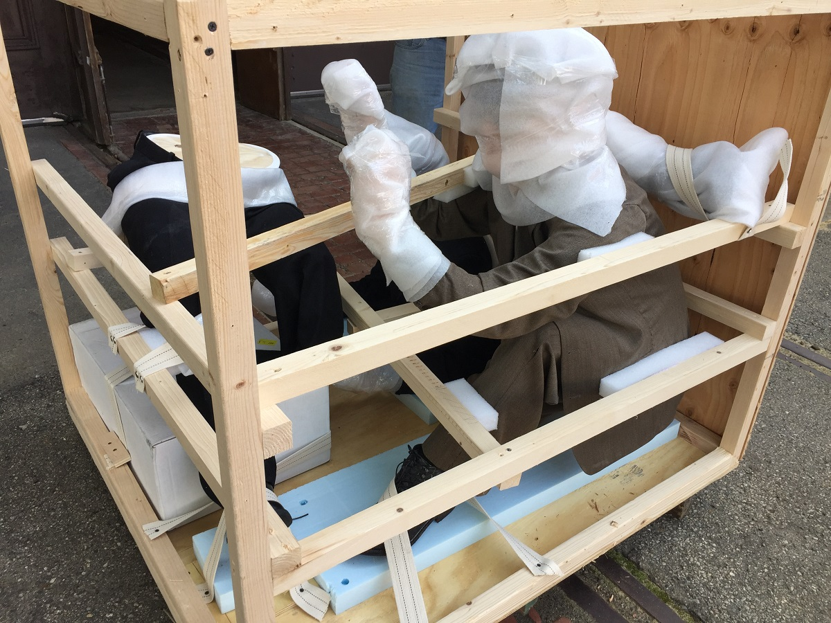 Open crate with two human-like figures swaddled in packing material