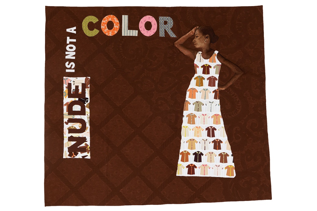"Brown quilt with quilted text ""NUDE IS NOT A COLOR"" and image of brown-skinned woman in pale dress covered with smaller images of shirts in many shades"