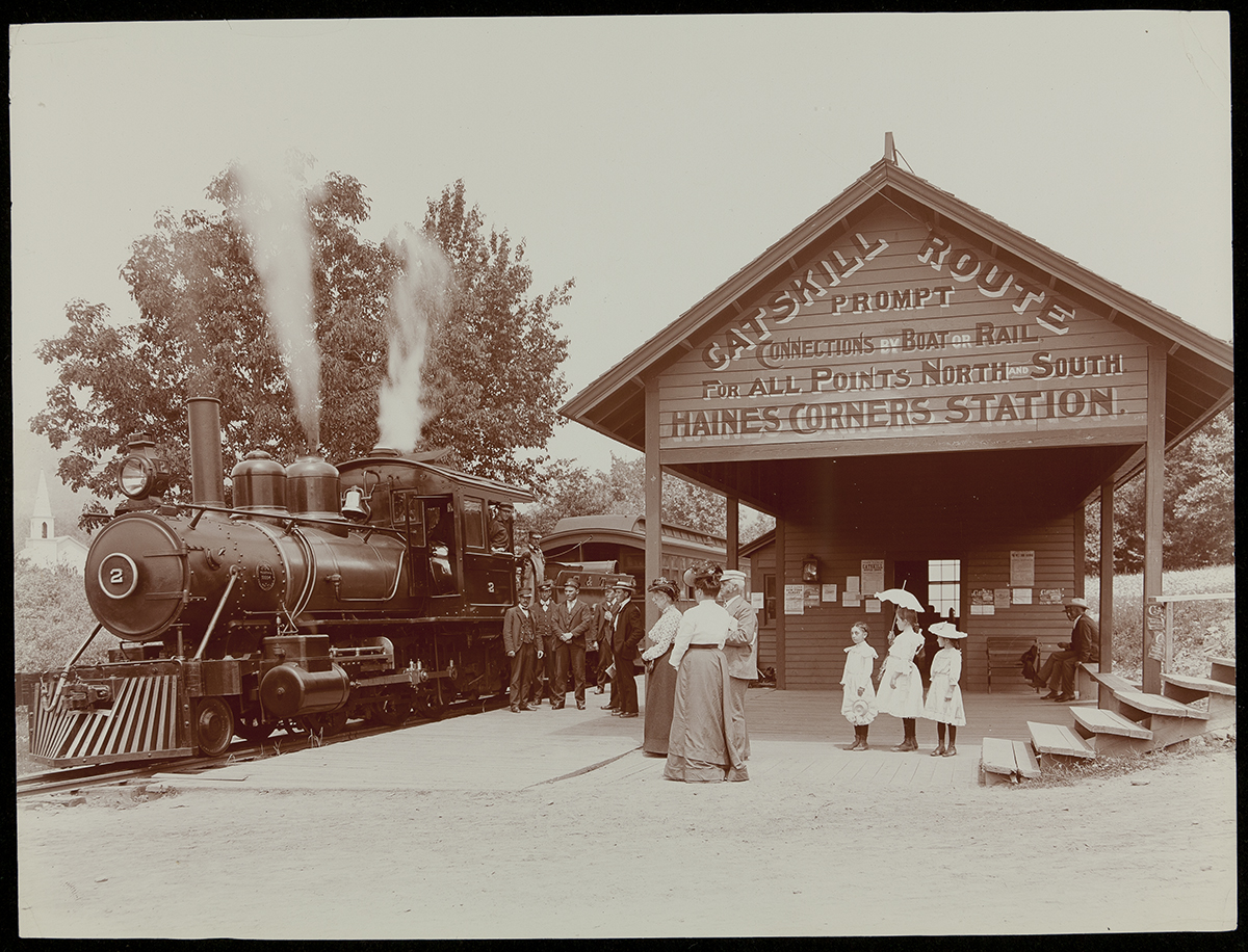 Photo of train with steam coming from it at tentpole-like station with a number of people standing around