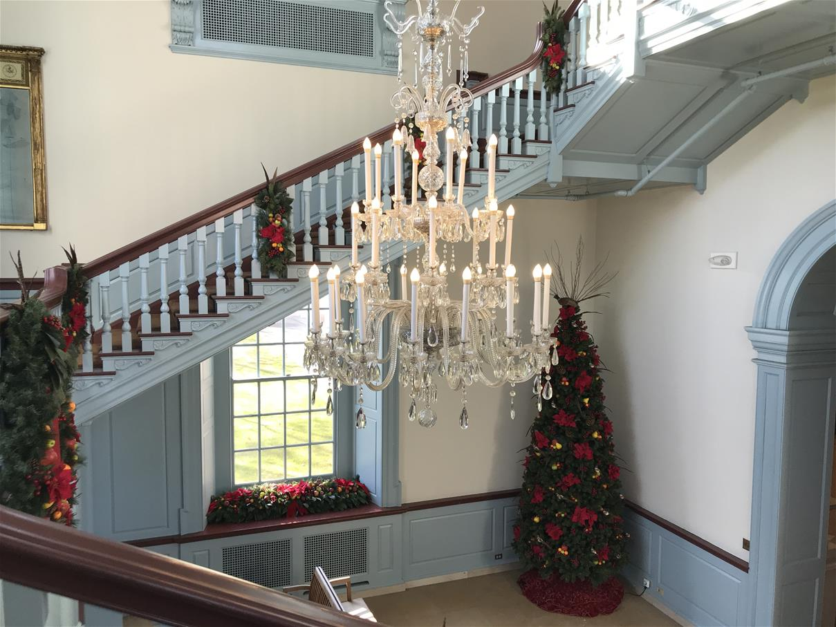 White-and-light-blue room with staircase and elaborate chandelier, decorated with Christmas trees and greenery