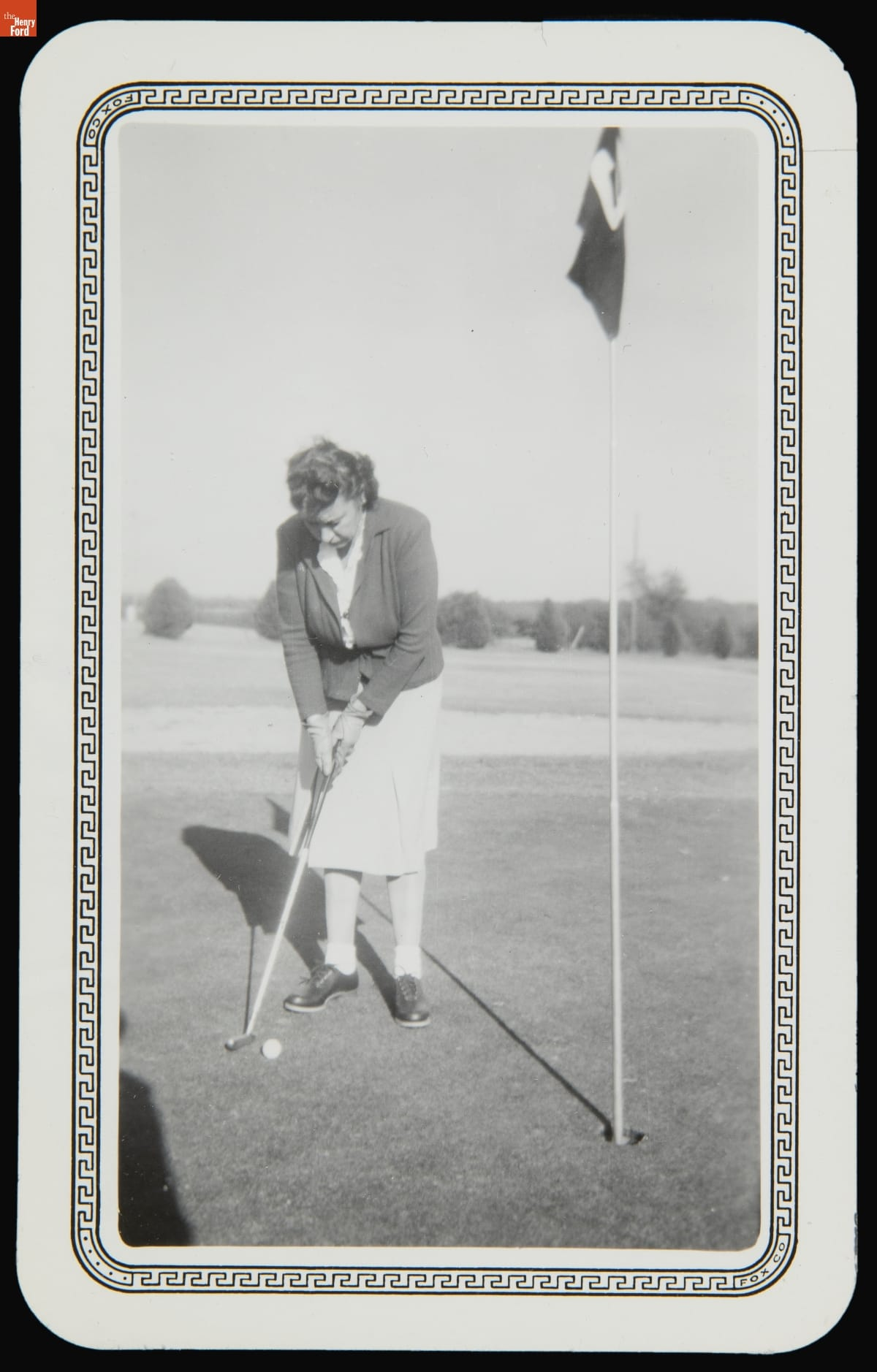 Woman in skirt and jacket bends over to putt a golf ball with hole marked with flag nearby