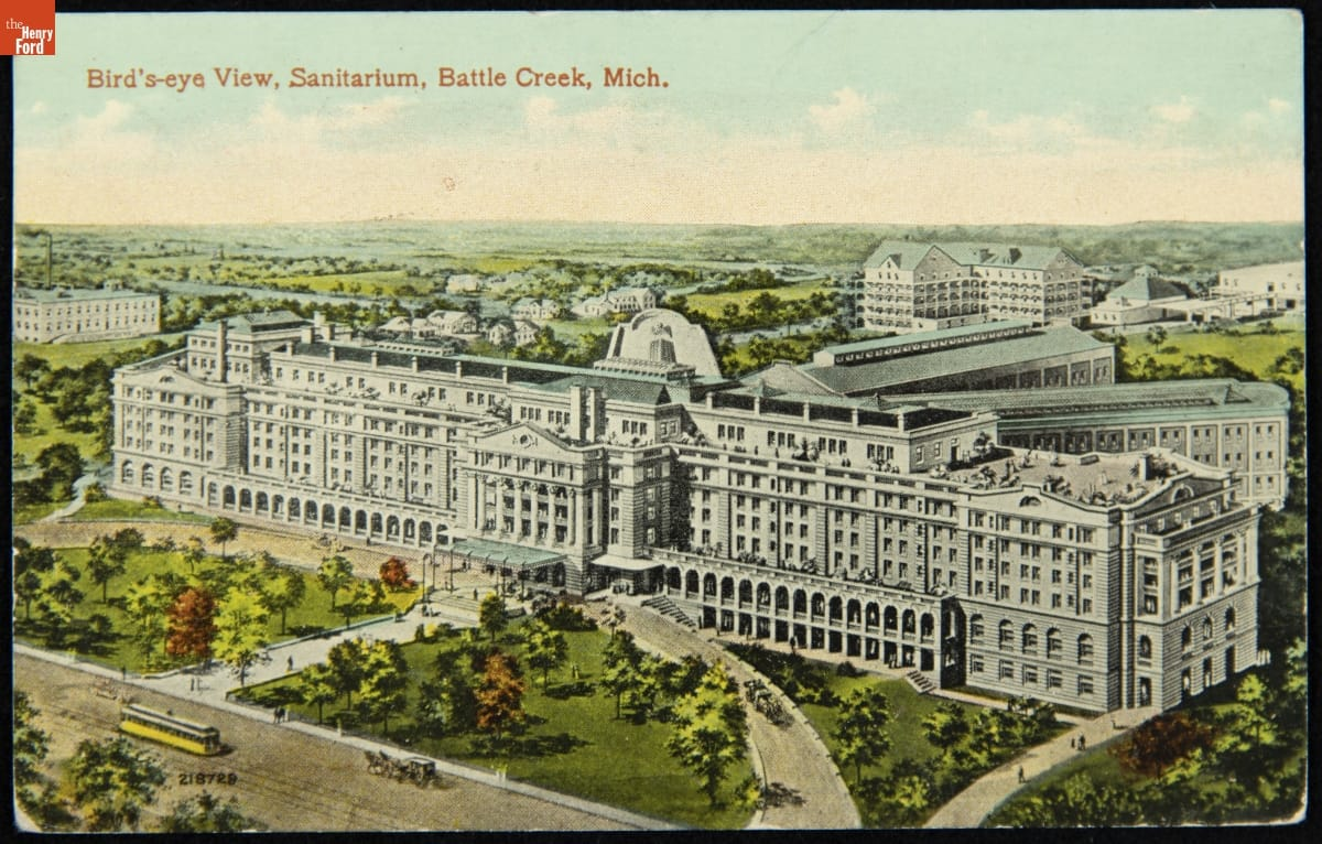 Color illustration of large white building complex surrounded by lawns, trees, and a few other buildings; contains text