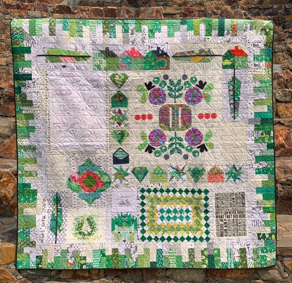 Quilt, primarily white with green border.