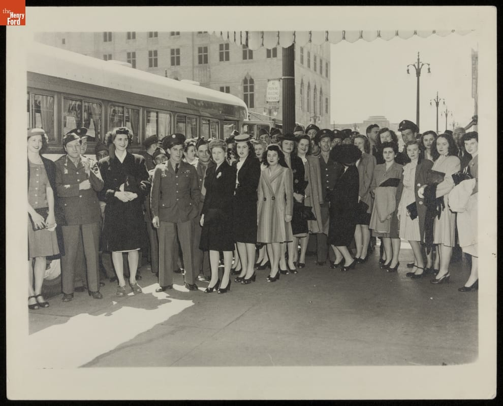 Group of men in military uniforms and women in dresses stand in front of a bus, with buildings and streetlights in the background
