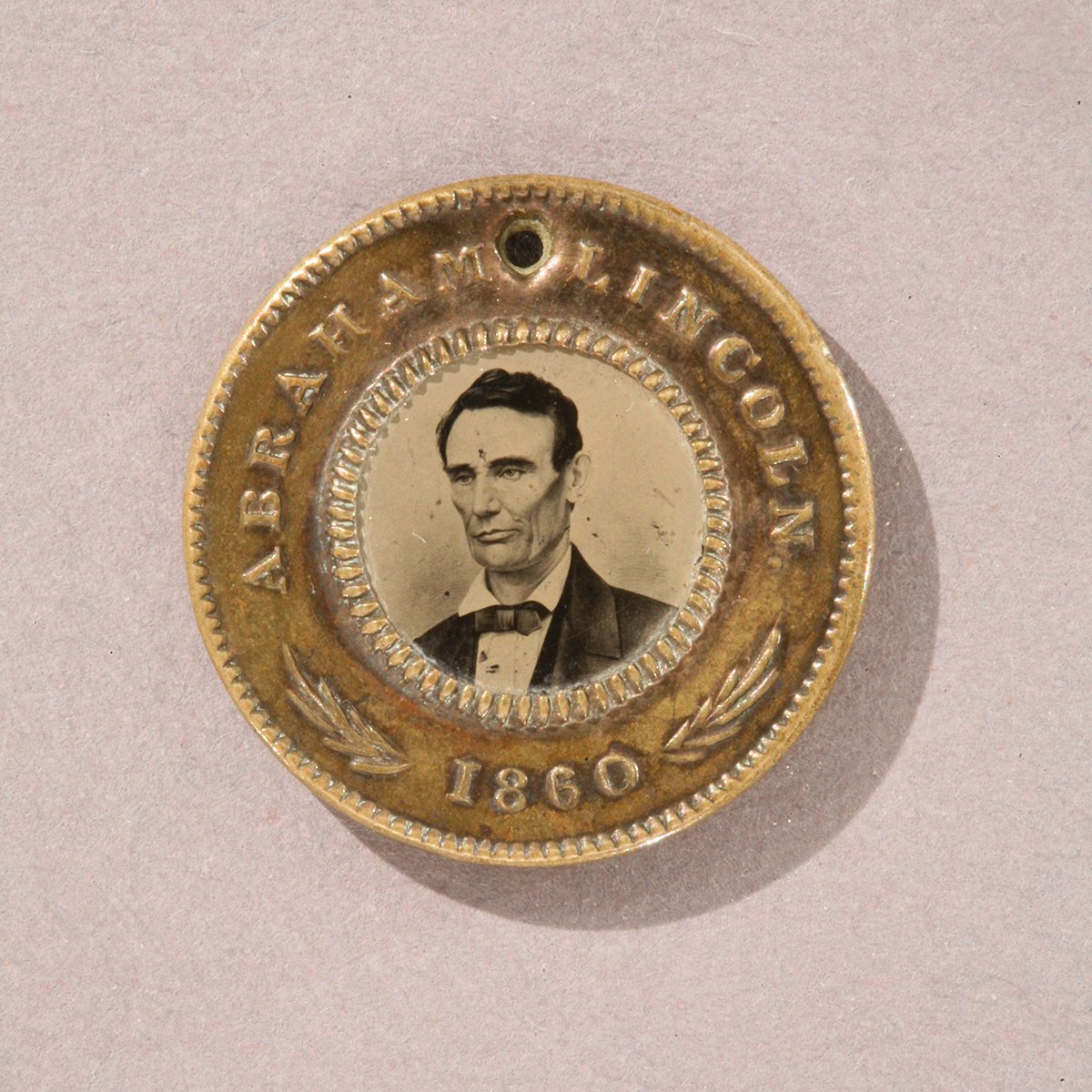 "Round gold token with image of man's shoulders and head in the middle and text ""Abraham Lincoln 1860"" around edge"