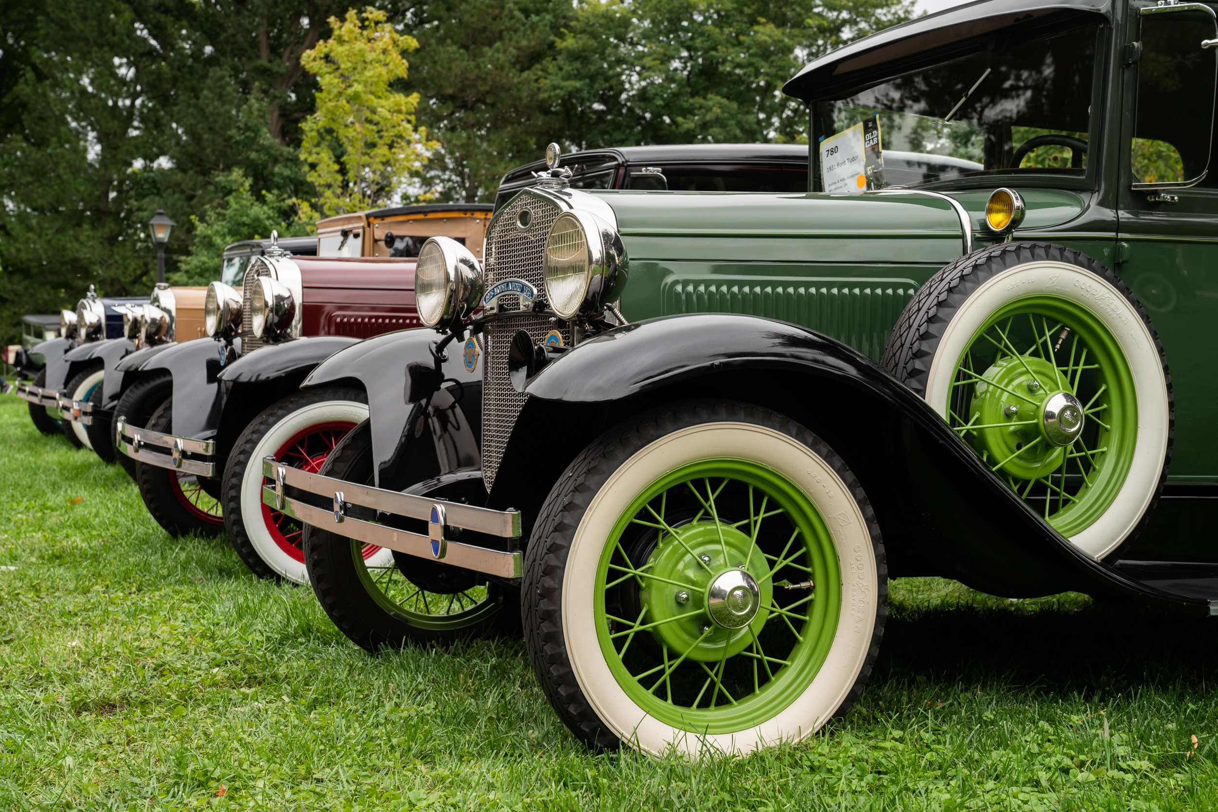 Row of antique vehicles parked on green grass