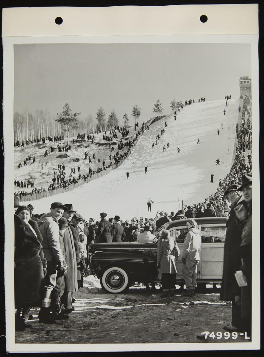 People on steep, snow-covered ski slope, with crowds on either side and more crowds and a car in the foreground