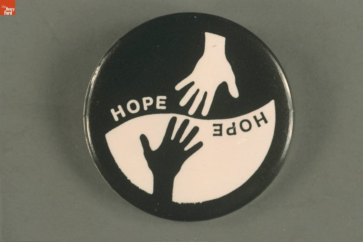 "Round button with top portion displaying a white hand and word ""hope"" on a black background, and the bottom half with the same elements but black and white reversed"