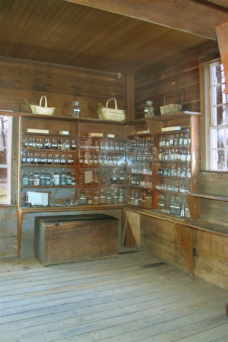 Corner of room with shallow wood shelves filled with baskets, bottles, and jars