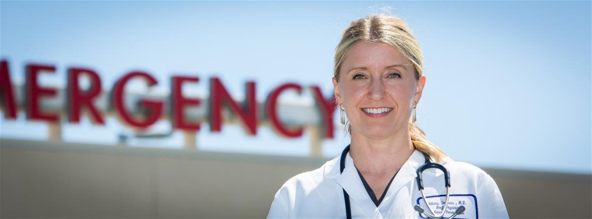 "Light-skinned blonde woman in medical coat with stethoscope around neck stands in front of sign reading ""EMERGENCY"""