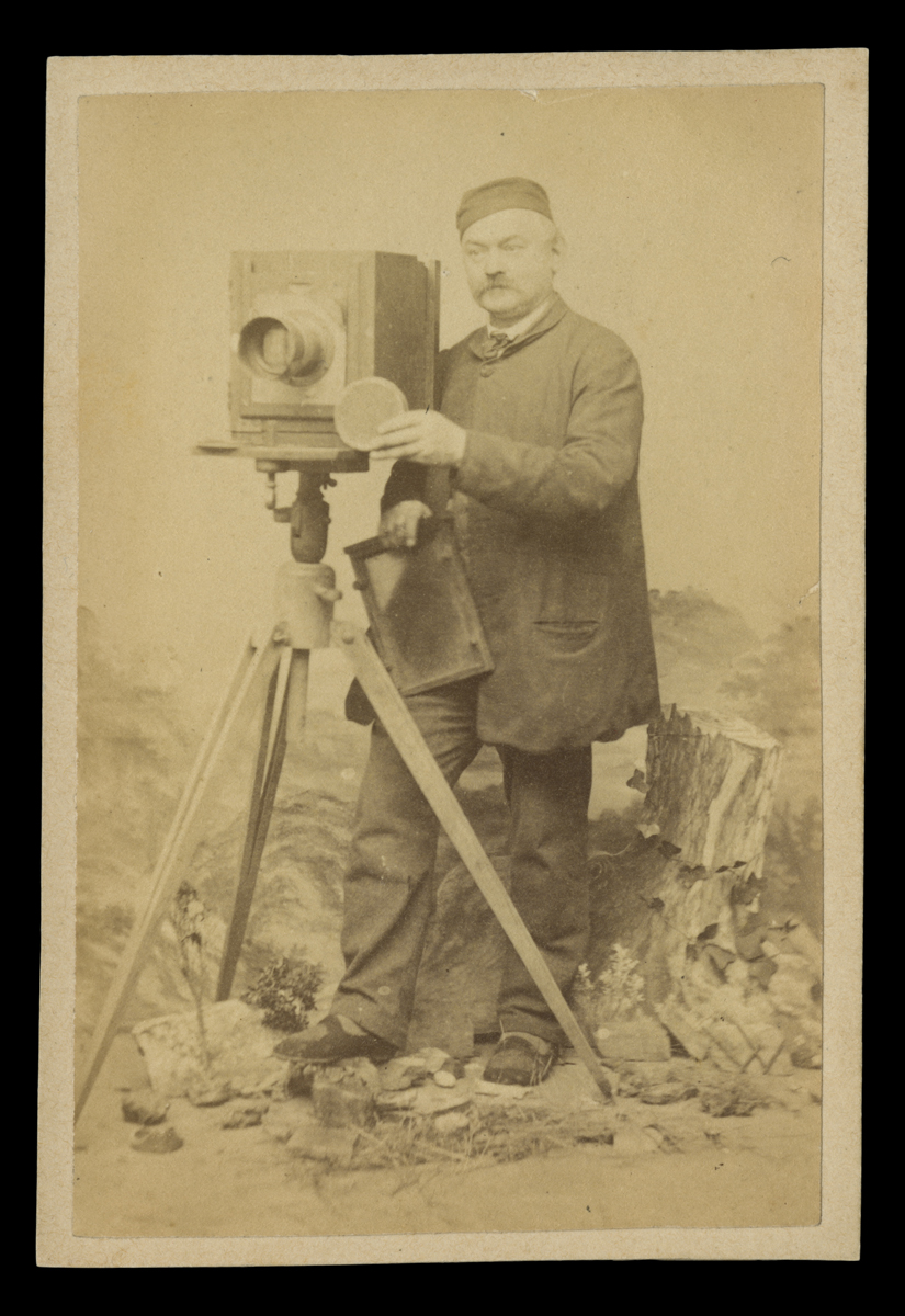 Man in smock and cap standing behind camera on tripod