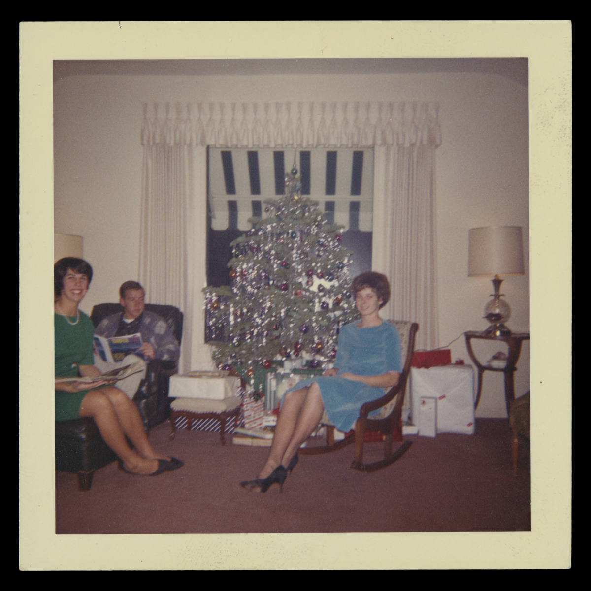 Two women and one man seated in a room around a silver aluminum Christmas tree