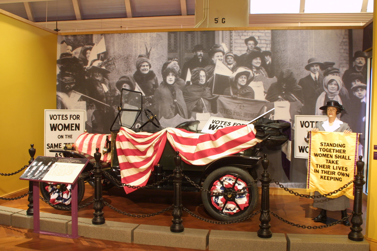 Model T covered in red and white striped bunting, in front of a photograph of women's suffrage advocates