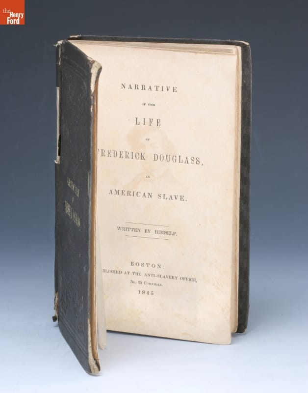 Book standing on end, open to title page, which contains text