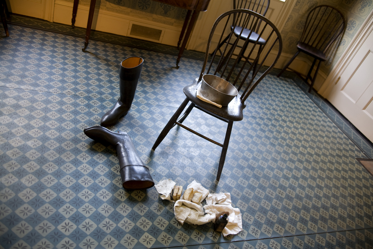Pair of boots lying on patterned blue floor next to chair with tub; rags nearby