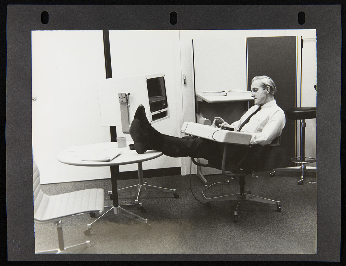 Page from three-ring binder containing photo of man sits in chair with attached console with feet up on a nearby table that also holds what appears to be a large monitor; office furniture around him