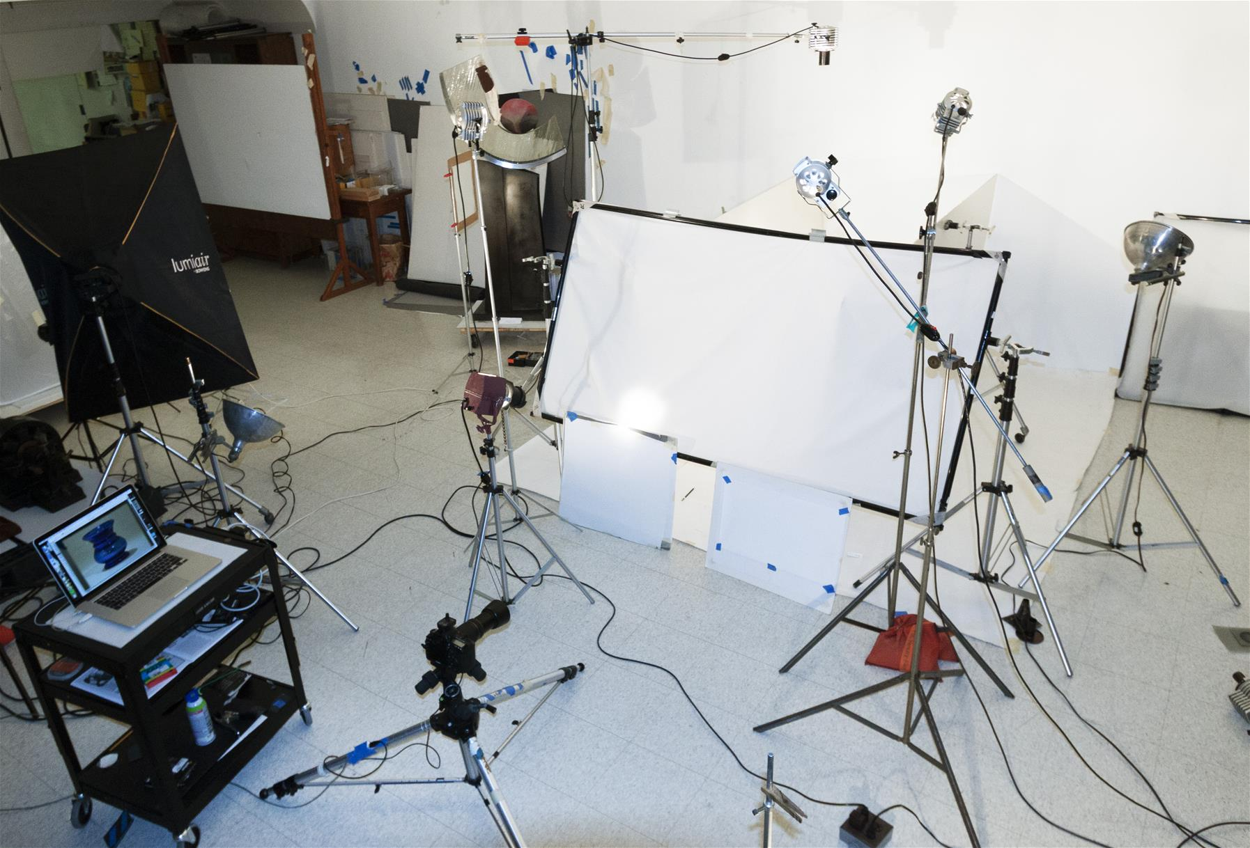 Photo studio with cart with laptop, many lights on stands, area blocked off with white paper