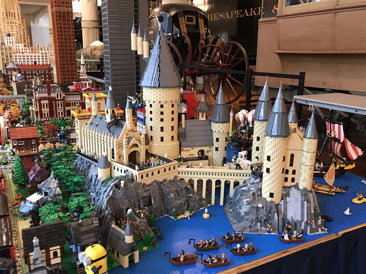 Extensive LEGO layout with boats and castle in foreground, buildings in background, and unrelated museum artifacts behind the layout