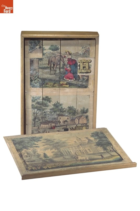 box, standing vertically with blocks with image on them in it; box lid lying in front with image on it
