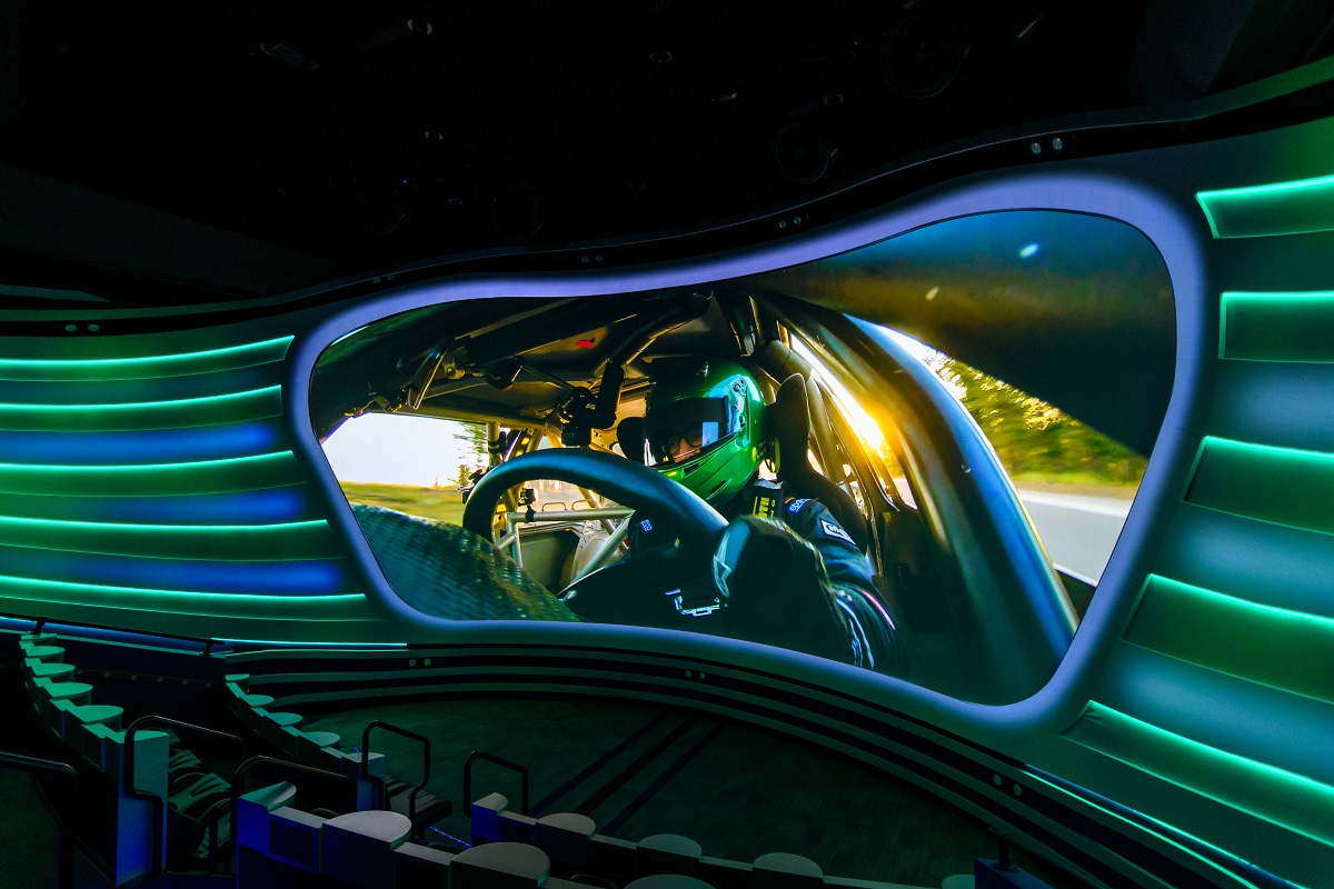 Curved theater with visor-shaped image of race car driver on screen and blue and green bars extending outward