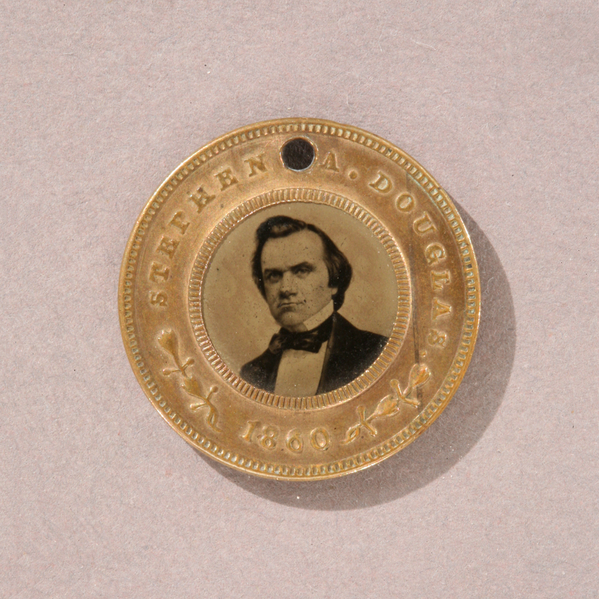 "Round gold token with image of man's shoulders and head in the middle and text ""Stephen Douglas 1860"" around edge"