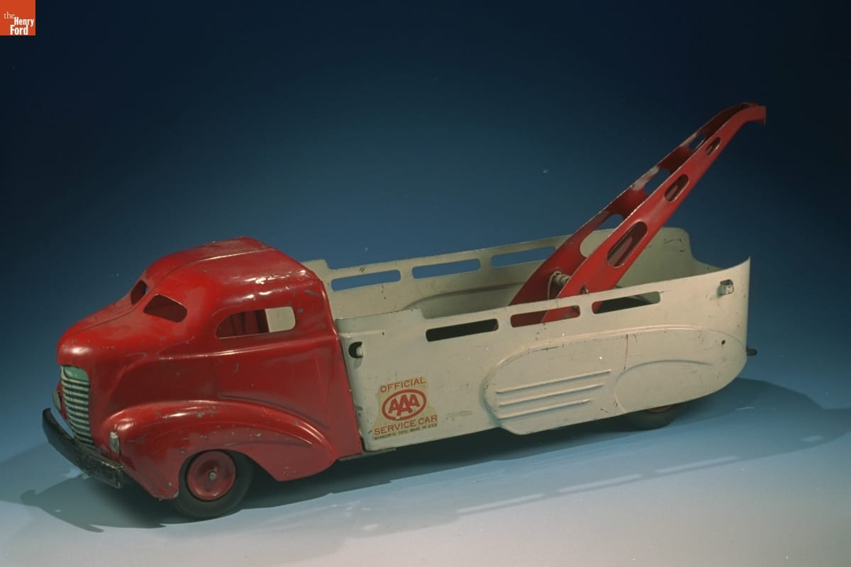 Toy truck with red cabin, white bed, and red winch in bed, with AAA logo on side