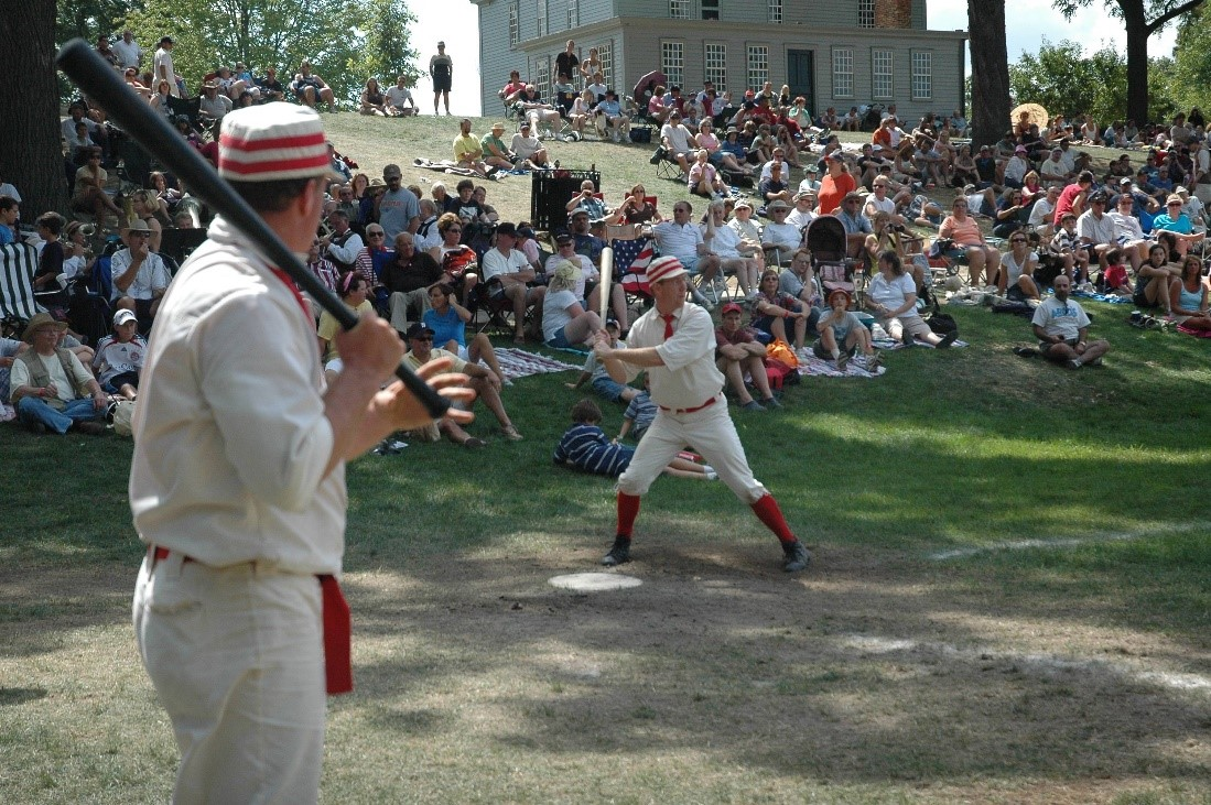 An historic base ball player holds a bat ready to swing as another stands nearby and a crowd looks on