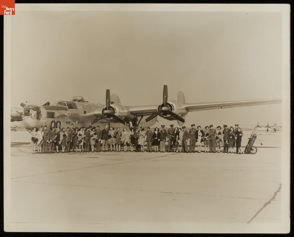 Large group of men and women pose in front of airplane on tarmac